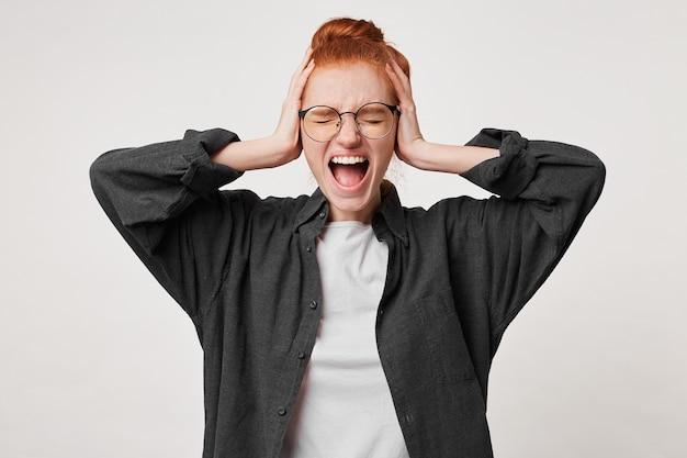 目を閉じて立っている若い赤毛の女性