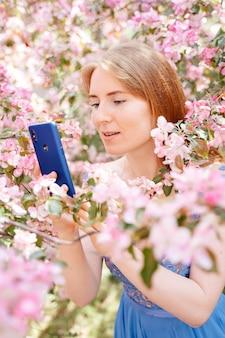 빨간 머리 소녀가 분홍색 사과 과수원을 배경으로 친구들과 인터넷에서 수다를 떨면서 파란 전화를 들고 있다 프리미엄 사진