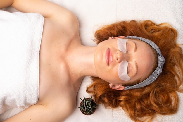 Молодая рыжеволосая женщина в белом полотенце и повязке на глазах расслабляется с закрытыми глазами