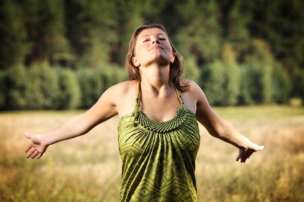 自然な緑の上でリラックスした若いリラックスした女性