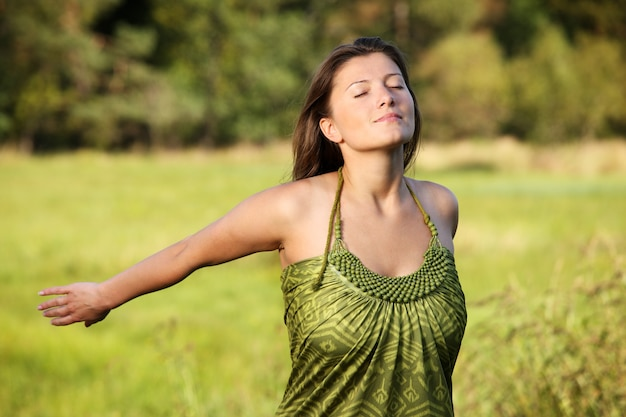 自然な緑の背景に笑みを浮かべて若いリラックスした女性