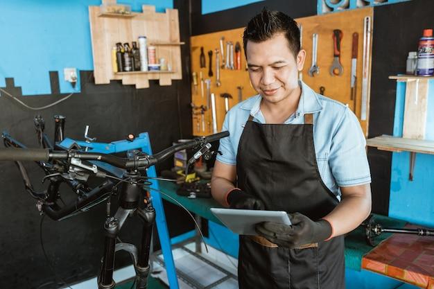 태블릿을 사용하여 작업복으로 앞치마를 입은 젊은 수리공