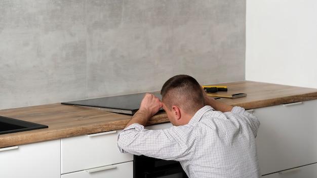 젊은 수리공이 콘크리트 벽이있는 현대적인 흰색 스칸디나비아 스타일 주방에 검은 색 인덕션 호브를 설치합니다. 전기 기사 님, 직접 해보세요. 가사.