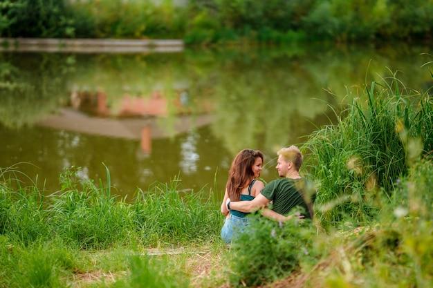 Молодая романтическая пара мужчина и женщина сидят в объятиях на берегу озера