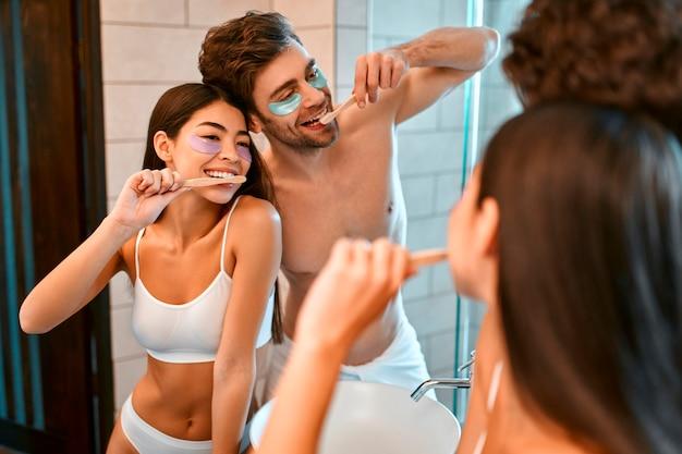 욕실에있는 젊은 로맨틱 커플은 거울 앞에서 양치질을하고 눈 밑에 보습 패치를 붙여 함께 즐겁게 지냅니다. 아침 루틴, 페이셜 및 바디 스킨 케어.