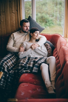 Молодая романтическая пара лежит дома на диване во время карантина. концепция самоизоляции.