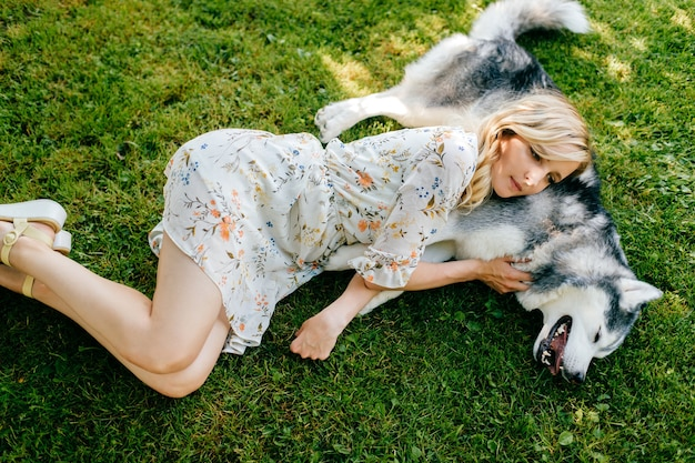 草の上に幸せな犬と一緒に横たわっている若いロマンチックな女性
