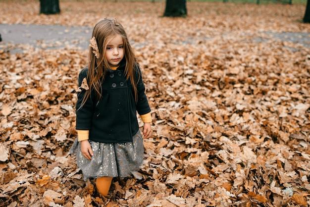 秋の公園でポーズをとって悲しい少女