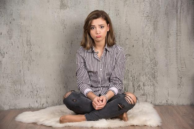 頬を吹く格子縞のシャツを着た若い悲しい女性。
