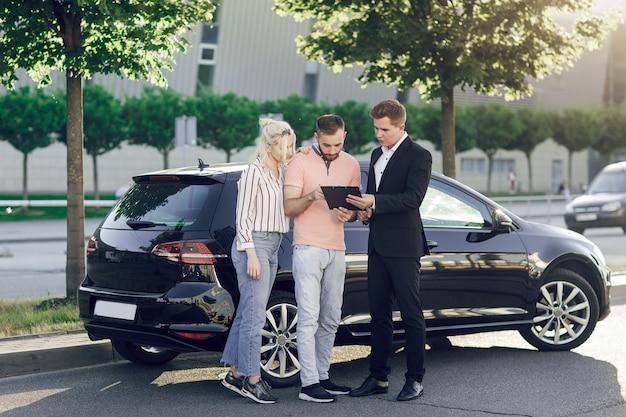 Молодой продавец показывает покупателям новую машину. счастливая пара, мужчина и женщина покупают новую машину. молодые люди подписывают документы на покупку машины.