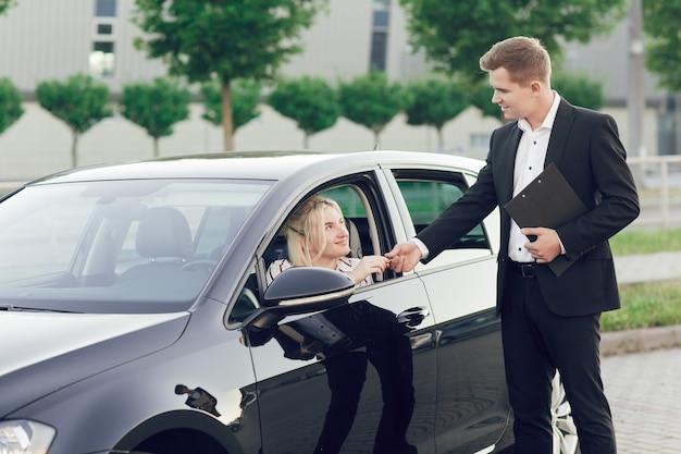 Молодой продавец показывает покупателям новую машину. счастливая женщина покупает новую машину. за рулем девушка сидит, продавец передает ей ключи.