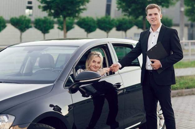 若いセールスマンが新しい車を顧客に見せます。幸せな女性は新しい車を購入します。若い女性がハンドルを握っていて、売り手は彼女に鍵を渡します。