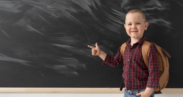 Юный школьник возле доски показывает указательным пальцем влево. на модном парне рубашка в клетку и легкие джинсы. на спине у ребенка коричневый рюкзак.