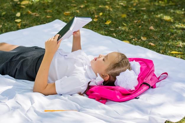 Юная школьница делает домашнее задание, лежа на одеяле и рюкзаке в солнечном осеннем парке. обучение детей на свежем воздухе. вернуться к школьной концепции