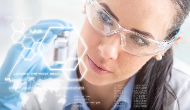 若い科学者が化学物質を調べます。化学式との未来的な科学的インターフェース。