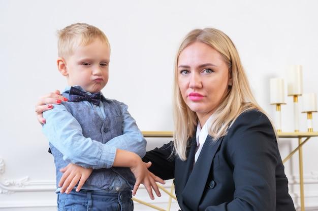 Молодая серьезная блондинка в черном пиджаке и маленький мальчик, изображающий бизнесмена