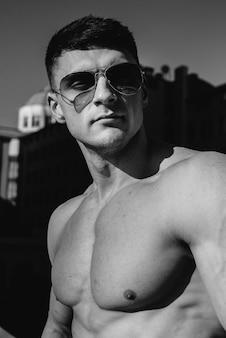 완벽한 복근을 가진 젊은 섹시한 운동선수가 화창한 날 밖에 있는 청바지에 토플리스 포즈를 취합니다. 건강한 생활 방식, 적절한 영양, 훈련 프로그램 및 체중 감량을 위한 영양. 검정색과 흰색.