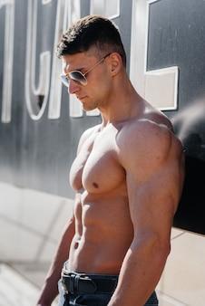 완벽한 복근을 가진 젊은 섹시한 운동선수가 화창한 날 밖에 있는 청바지에 토플리스 포즈를 취합니다. 건강한 생활 방식, 적절한 영양, 훈련 프로그램 및 체중 감량을 위한 영양.