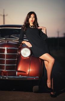 Молодая сексуальная брюнетка с длинными ногами в черном платье и туфлях на каблуках стоит возле бордового ретро-автомобиля на проселочной дороге поздним вечером