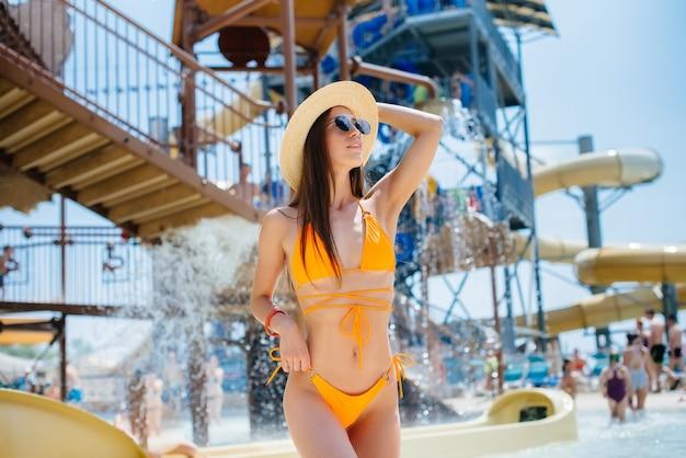 Молодая сексуальная девушка в очках и шляпе счастливо улыбается на фоне большого и современного аквапарка в солнечный день. счастливого отпуска. летний отдых и туризм.