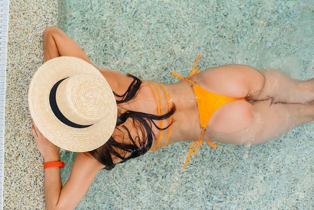 안경을 쓰고 모자를 쓴 섹시한 소녀가 화창한 날 크고 현대적인 워터파크를 배경으로 행복하게 웃고 있습니다. 행복한 휴가 휴가. 여름 휴가 및 관광.