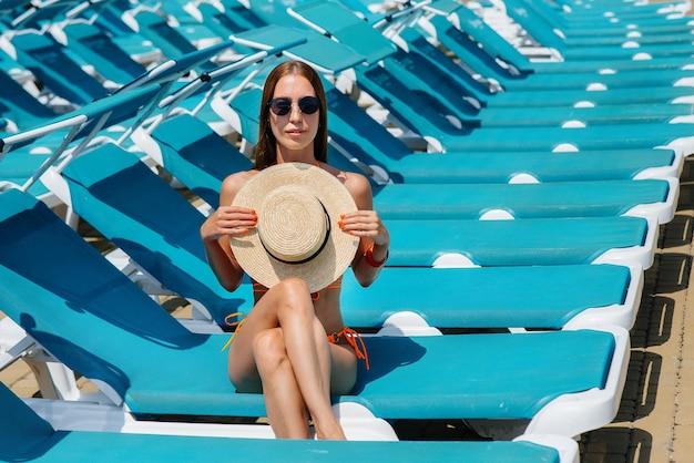 안경을 쓰고 모자를 쓴 섹시한 소녀가 화창한 날 일광욕용 라운저에서 행복하게 웃고 있습니다. 행복한 휴가 휴가. 여름 휴가 및 관광.