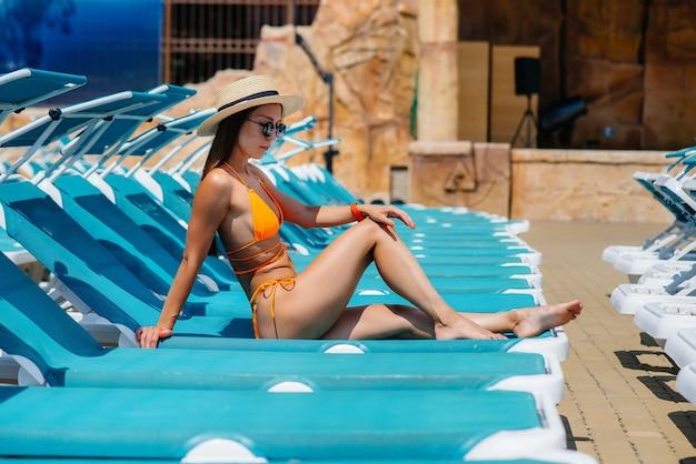 Молодая сексуальная девушка в очках и шляпе счастливо улыбается и загорает на шезлонге в солнечный день. счастливого отпуска. летний отдых и туризм.