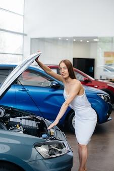 若いセクシーな女の子が購入する前に車のエンジンを検査します。自動車販売店で新車を購入する。