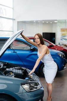 若いセクシーな女の子は購入する前に車のエンジンを検査します。自動車販売店で新車を購入する。