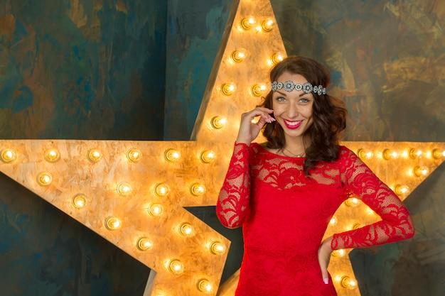 고급스러운 빨간 드레스와 하이힐에 붉은 입술을 가진 젊은 섹시한 여자는 금색과 밝은 별이있는 풍부한 스튜디오 인테리어의 의자에 앉아