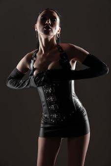 Молодая сексуальная женщина в черном кожаном корсете с открытой грудью позирует, прикрывая ее руками на темном фоне