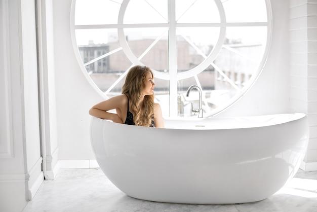 黒いレースの下着を着た若いセクシーな女性がお風呂に座っています