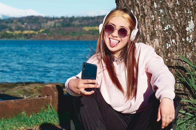 木の下で休んでいる間、彼女の電話が彼女の舌を突き出して彼女自身の写真を撮る若いスケーター