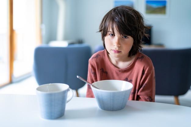 잠옷을 입은 어린 졸린 소년이 등교 전 아침에 집에서 아침을 먹고 있습니다. 어린이를 위한 건강식.