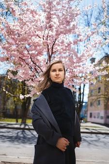長いウェーブのかかった髪と灰色のコートを着たスニーカーの若い細い女性モデルは、背景とポーズで美しいピンクの花が咲く低木の近くの通りに立っています。