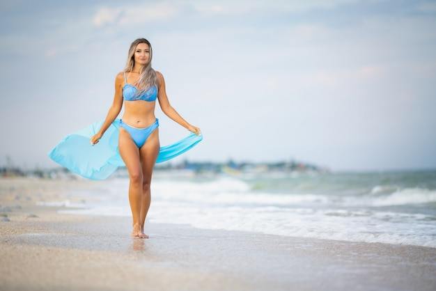 Молодая стройная загорелая девушка со светлыми волосами в нежном голубоватом купальнике и ярко-голубом платке гуляет по пляжу у кромки морской воды, наслаждаясь теплым летом