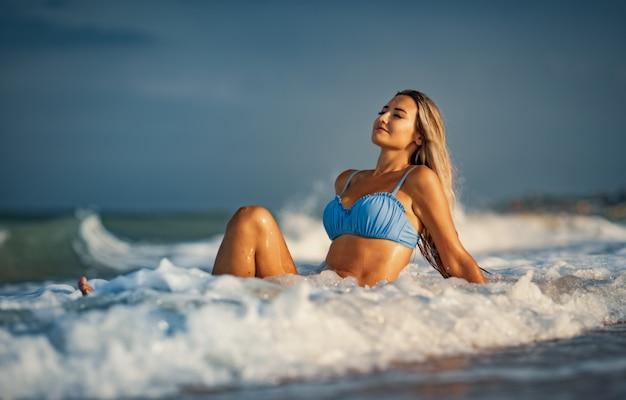 Молодая стройная загорелая девушка со светлыми волосами в нежном голубоватом купальнике сидит на песке у моря, наслаждаясь всплеском свежих прохладных волн синего моря