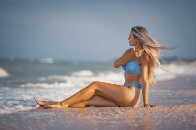 青い海の新鮮な涼しい波のスプラッシュを楽しんで海の近くの砂の上に座って、穏やかな青みがかった水着でブロンドの髪の若い日焼けした少女