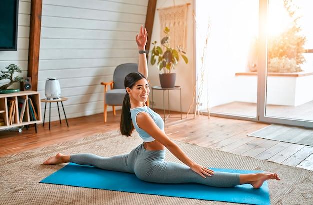 Молодая стройная женщина делает шпагат, чтобы размять ноги. радостная талантливая женщина делает шпагат в гостиной дома. здоровый образ жизни, концепция спорта.