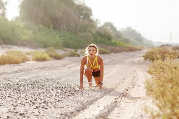 Молодая стройная женщина в спортивной одежде готовится к бегу с самого начала