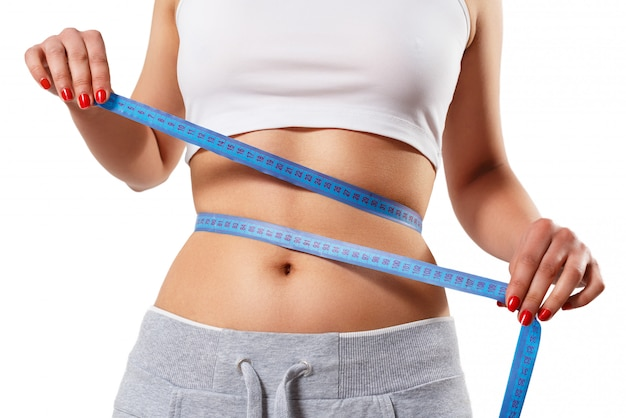 젊은 날씬한 여자는 센티미터 테이프로 허리를 측정합니다. 흰 벽에 절연