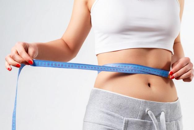 若い細身の女性がセンチメートルのテープで腰を測っています。白の上