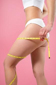 ほっそりした若い女性が腰の飛行円周を測定します。ピンクの背景に分離。