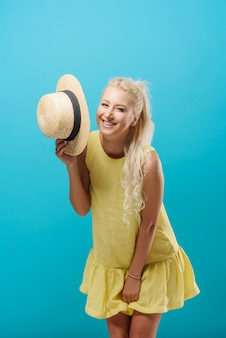 夏の黄色のドレスを着て、青い空間で帽子をかぶっている金髪の若い細身の女性モデル。モデルののんきな楽しみ