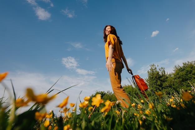 날씬한 젊은 여성이 알레르기가 없는 노란색 들판 바닥에서 푸른 하늘을 배경으로 서 있습니다.