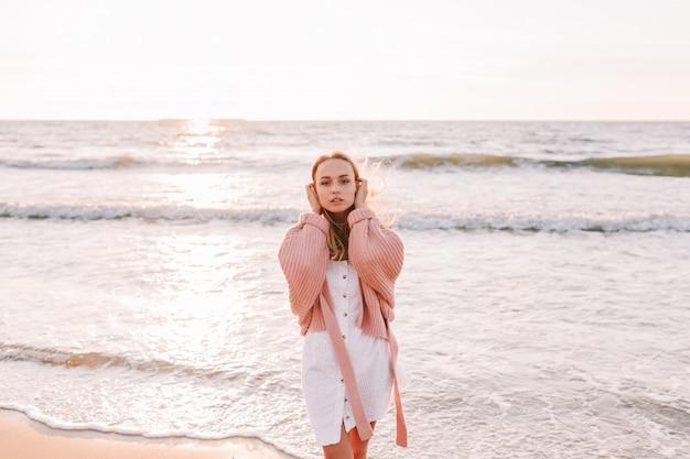 若いほっそりした女性がビーチまたは海に一人で立っています。暖かいセーターを着た女性。トーン。