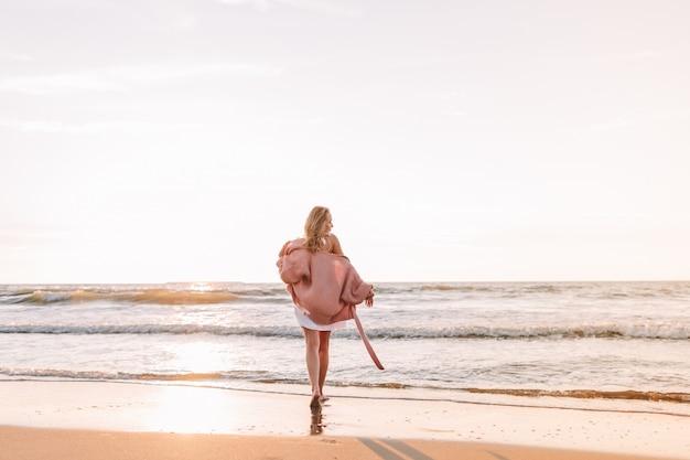 若いほっそりした女性がビーチまたは海に一人で立って、地平線を見ます。暖かいセーターを着た女性。トーン。