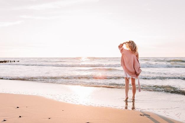 若いほっそりした女性がビーチまたは海に一人で立って、地平線を見ます。暖かいセーターを着た女性。