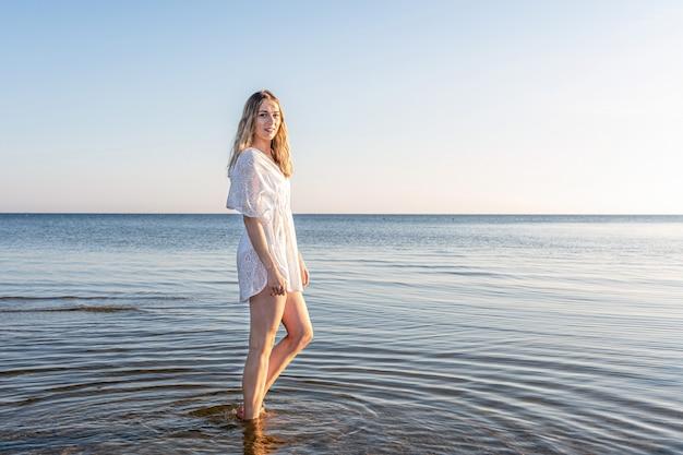 Молодая стройная и чувственная женщина просыпается у моря на пляже