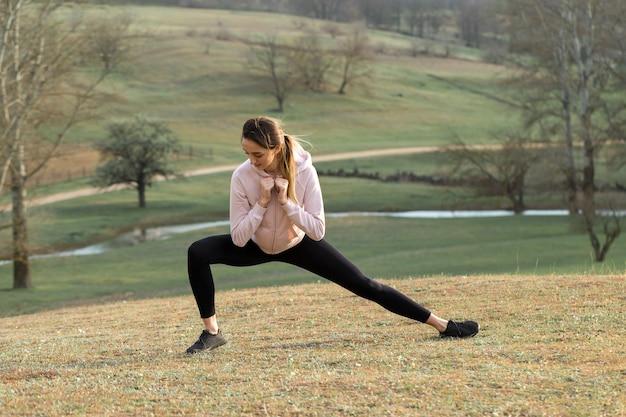 スポーツウェアの若いスリムな運動の女の子は、一連のエクササイズを実行します。緑の春の牧草地の丘を背景にしたフィットネスと健康的なライフスタイル。